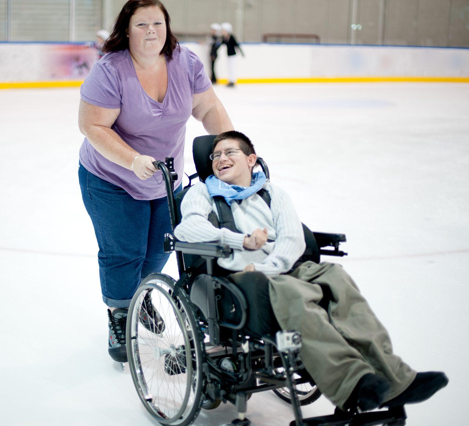 Funktionshindrad ung man i rullstol åker skridskor tillsammans med sin personliga assistent.