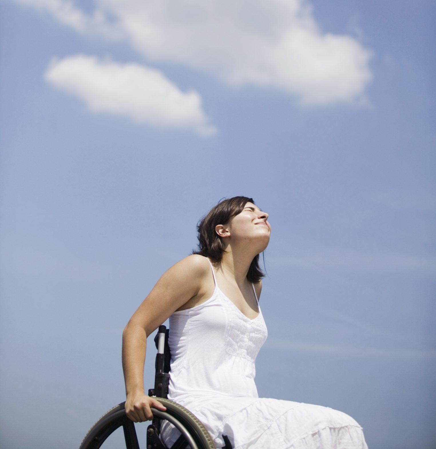 Kvinna i rullstol kisar upp mot solen på en blå himmel.