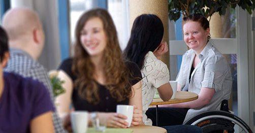 Rullstolsburen kvinna samtalar med en annan kvinna på ett kafé.