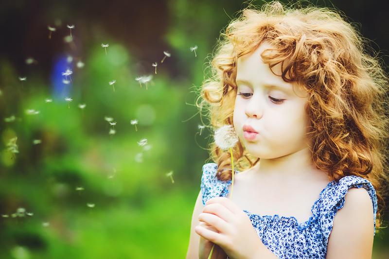 Liten flicka med lockigt hår blåser fröna ur en maskros.