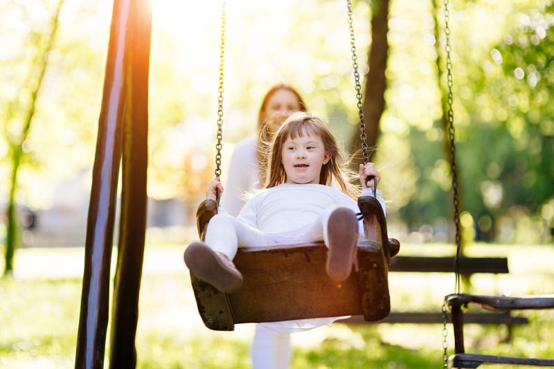 Liten flicka med Downs syndrom blir gungad av sin personliga assistent en fin sommarkväll.