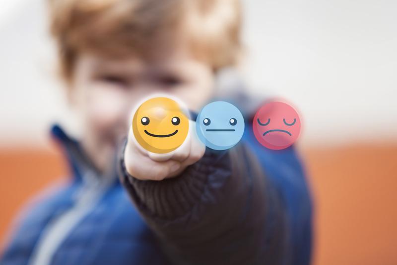 Pojke som betygsätter med hjälp av smileys på en genomskinlig pekskärm.